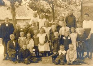 Foto 2, School te Westergeest, Antje van der Veen (met ketting) en kruisje op schouder staat naast het meisje waar de juffrouw de hand van vasthoud